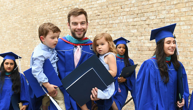 A graduate poses with his two small children