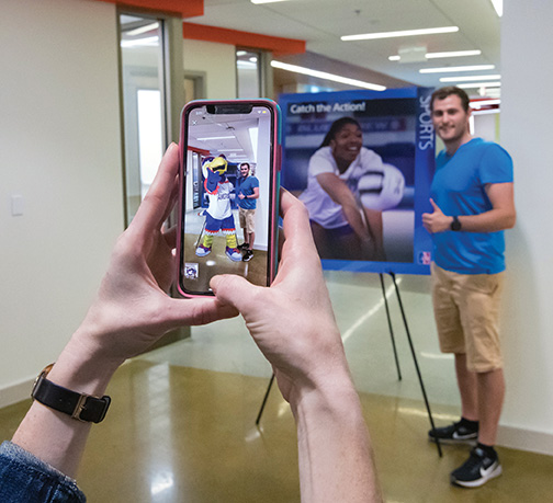 A prospective student poses with an augmented reality Clawed mascot