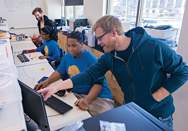 Students work at computer terminals with assistance from AU faculty