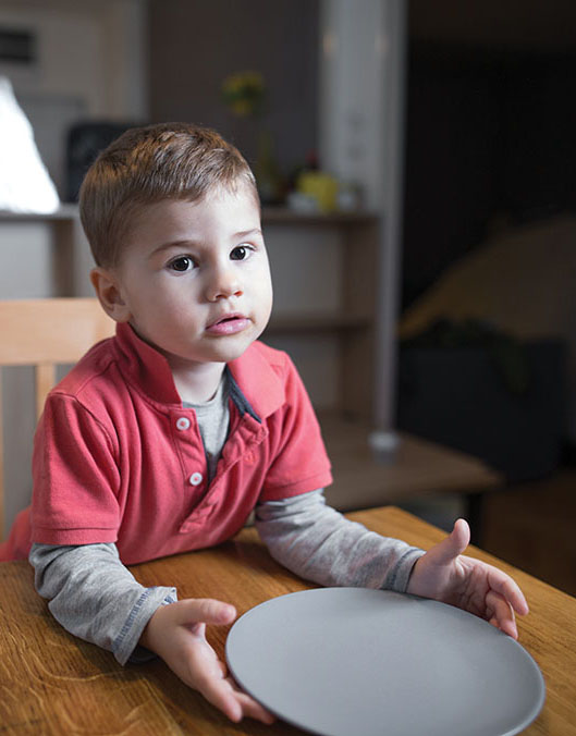 Child sits at a table with an empty plate
