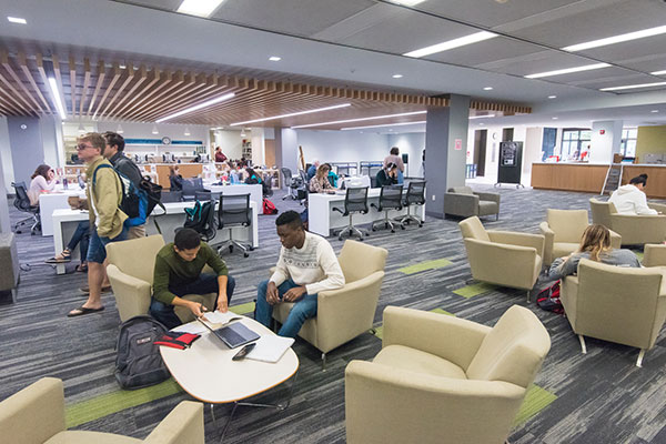 Students study in comfortable chairs in a light-filled library