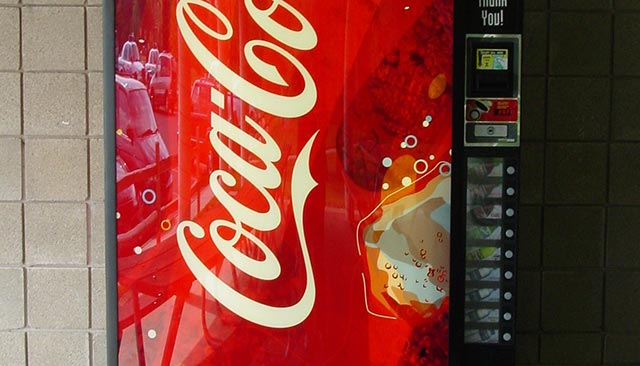A vending machine with the Coca-Cola logo partially visible