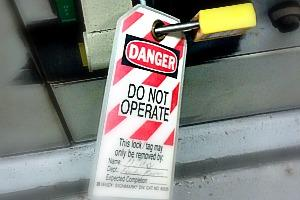 "A tag locked onto some equipment with the words, ""Danger, Do Not Operate. This lock may only be removed by"" and then a faded out signature"
