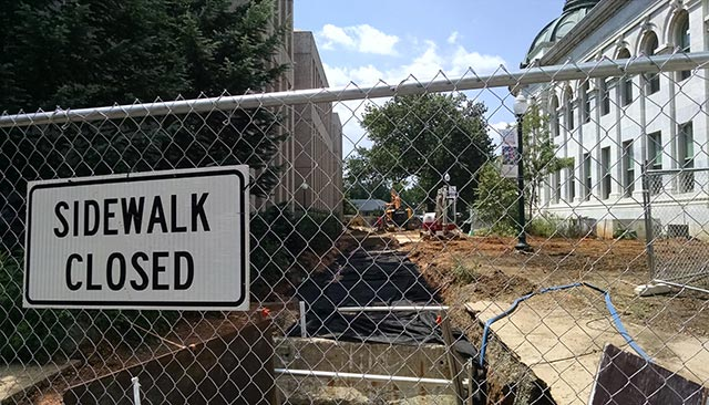 A sign on a fence reads, 'Sidewalk Closed,' with construction in the background