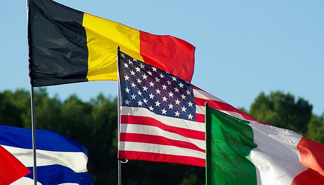 Cuban, Belgian, American, and Italian flags, with sky as background