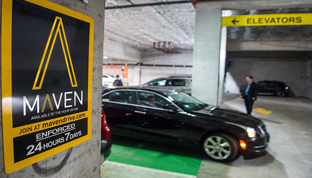 A Maven rental car, leaving a parking garage in front of a sign for Maven.