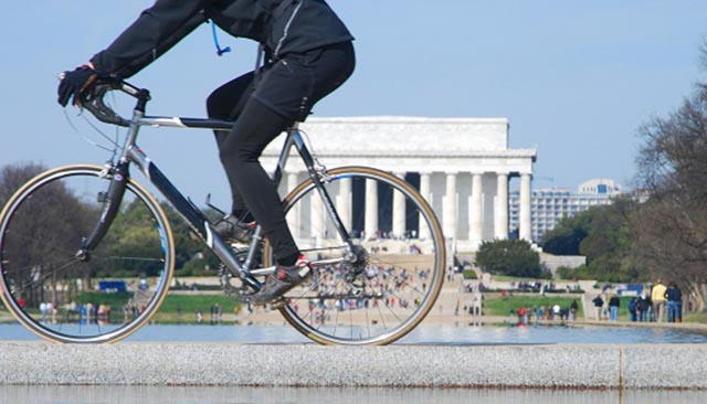 A cyclist rides past the Lincoln Memorial