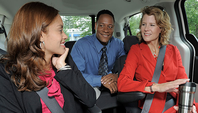 Group of individuals in a carpool and smiling.