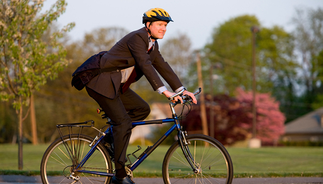 Man in a suit on a bicycle.