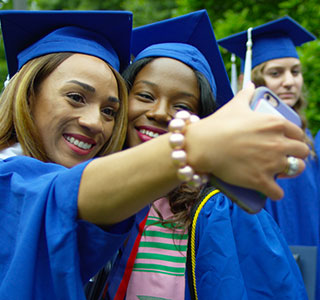 Graduates take a selfie during commencement