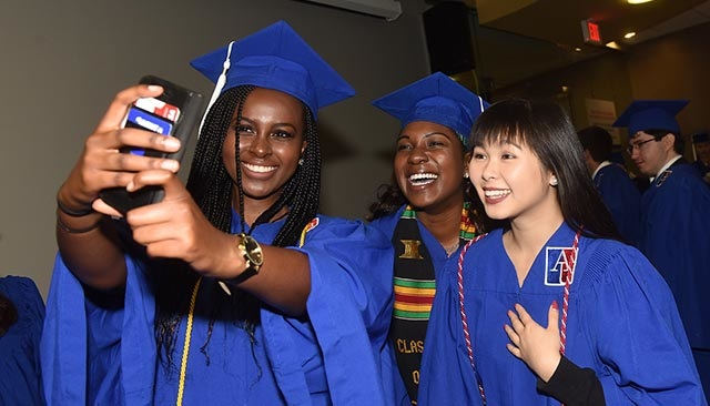 Three graduating students pose for a selfie together.