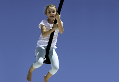 A scared child swinging on a rope.