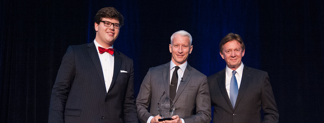 A student leader, Anderson Cooper, and President Kerwin on stage