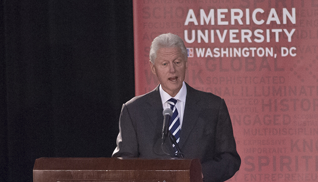 President Bill Clinton speaks in front of an American University banner