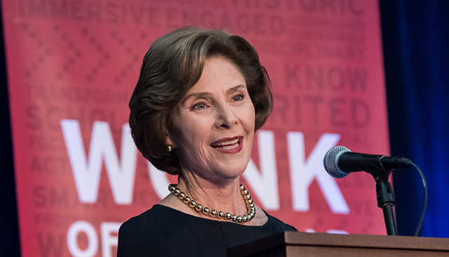 Laura Bush speaking at a podium, a wonk banner in the background