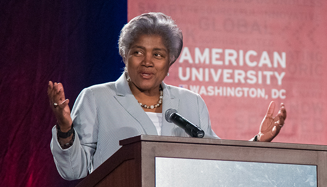 Donna Brazile speaks at a podium in front of an American University banner