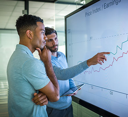 Two young men looking at an analytical chart on a large screen