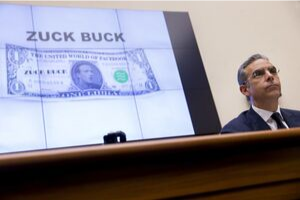 a projected display of paper money with Mark Zuckerberg's face on it and the words