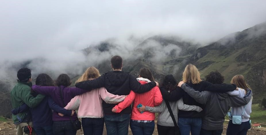 Row of students with backs to camera looking at Ecuadorian mountain vista