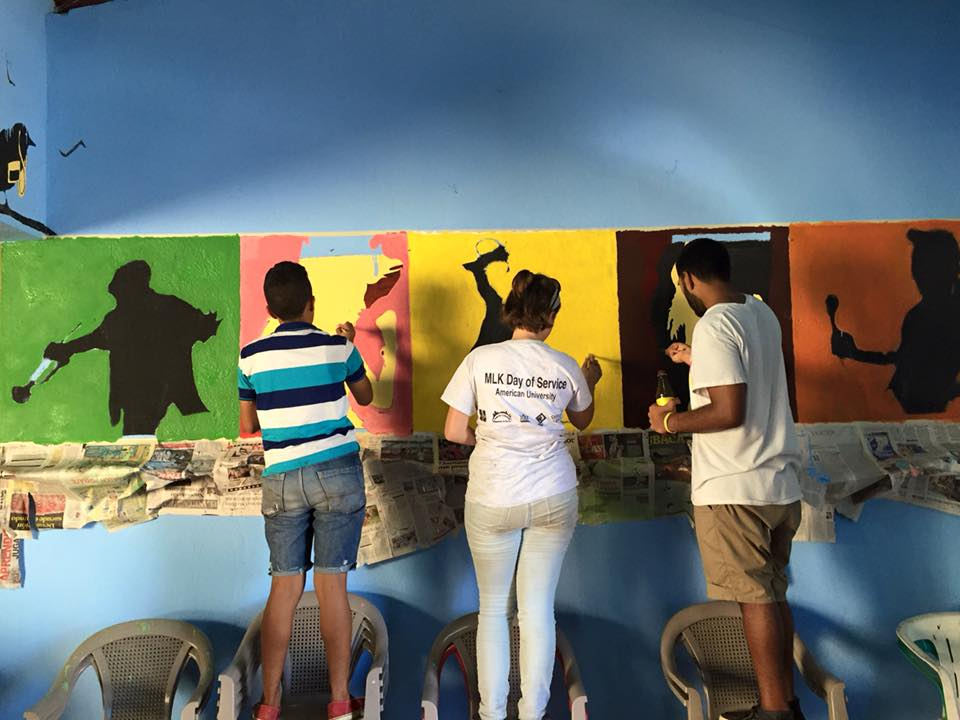 Three people with backs to viewer, painting a wall.