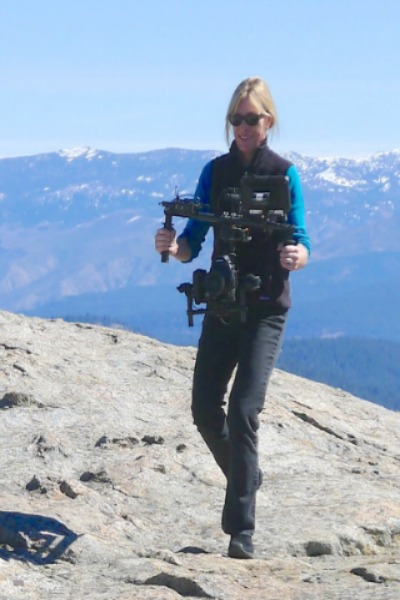 Professor Maggie Stogner filming on top of a mountain