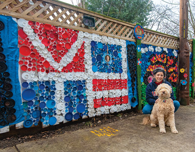 Karen Lash and her dog Lucky in front of her backyard mosaics