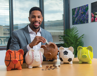 Romone Penny inserts money into a piggy bank shaped like a football.