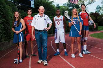 Ted Riggelheim stands in front of several AU student-athletes