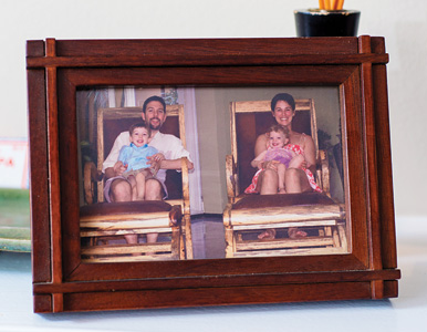 the Tomaseks and their children in two wooden chairs