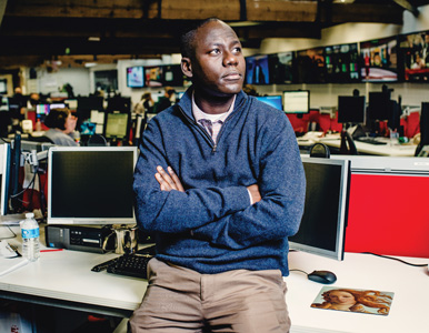 Derek Karikari sits on his desk at the AP newsroom in London