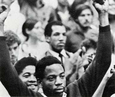 African American student with arms raised at a rally