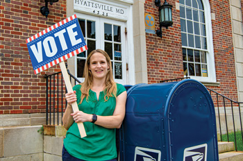 Elizabeth Daigneau stands in front of a blue mail collection bin holding a vote sign