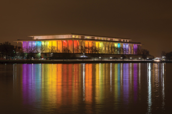 Kennedy Center at night, bathed in rainbow lights