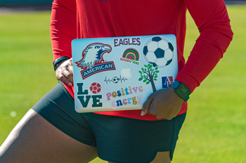 Marsha Harper holds a laptop decorated with motivational stickers