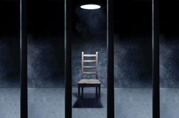 an empty interrogation chair in a prison cell