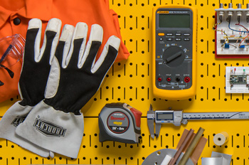 Gloves and welding apron, digital multimeter, circuit, tape measure, and calipers