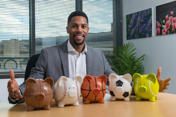 Romone Penny inserts money into a piggy bank shaped like a football