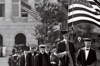 Old black and white of commencement procession on campus