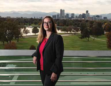 Christine Hernandez stands on a balcony with downtown Denver in the background