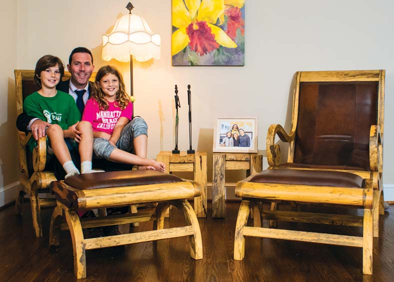Adam Tomasek and his two young children sit in a chair