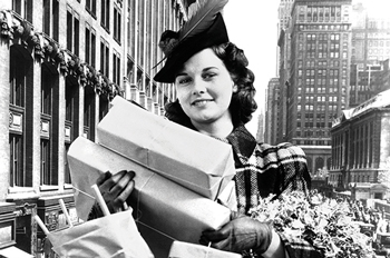 Black and white photo of a woman holding several gift boxes