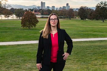 Christine Hernandez stands in a park with downtown Denver in the background