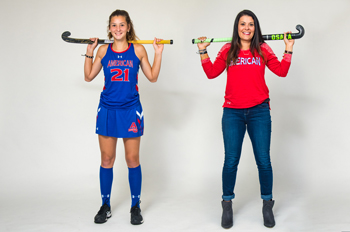Aidan Rossman and Abbie Rossman hold field hockey sticks over their shoulders