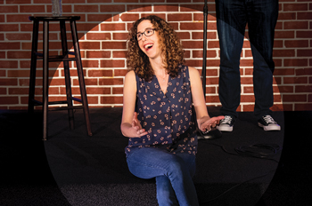 Allyson Jaffe sits and laughs on the DC Improv stage
