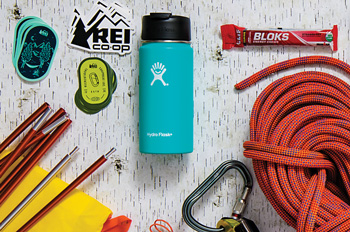 REI stickers, a tent, a coffee thermos, energy chews, a belaying device, climbing rope, car keys, a fleece jacket, a laptop, a smart phone, trail running shoes, bike lube, and a bike helmet