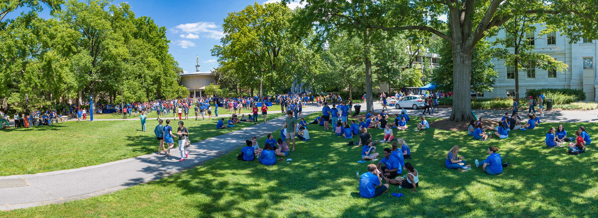New students relax on the quad. Key Spiritual Life Center (also known as the flaming cupcake because of its bronze flame) is visible.