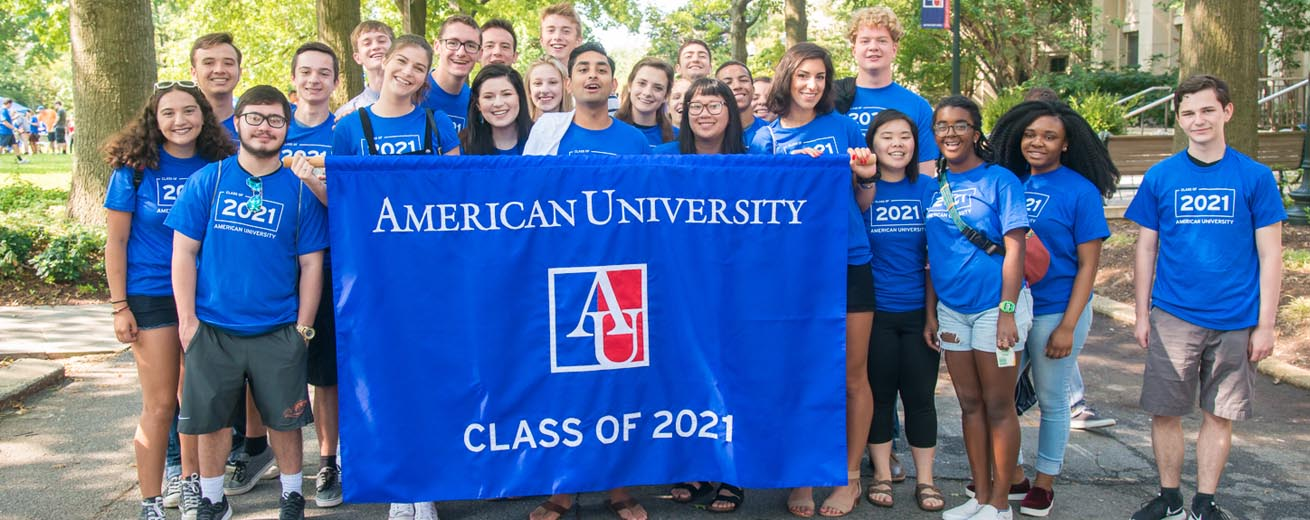 Members of the Class of 2021 poses with a banner that says American University Class of 2021.