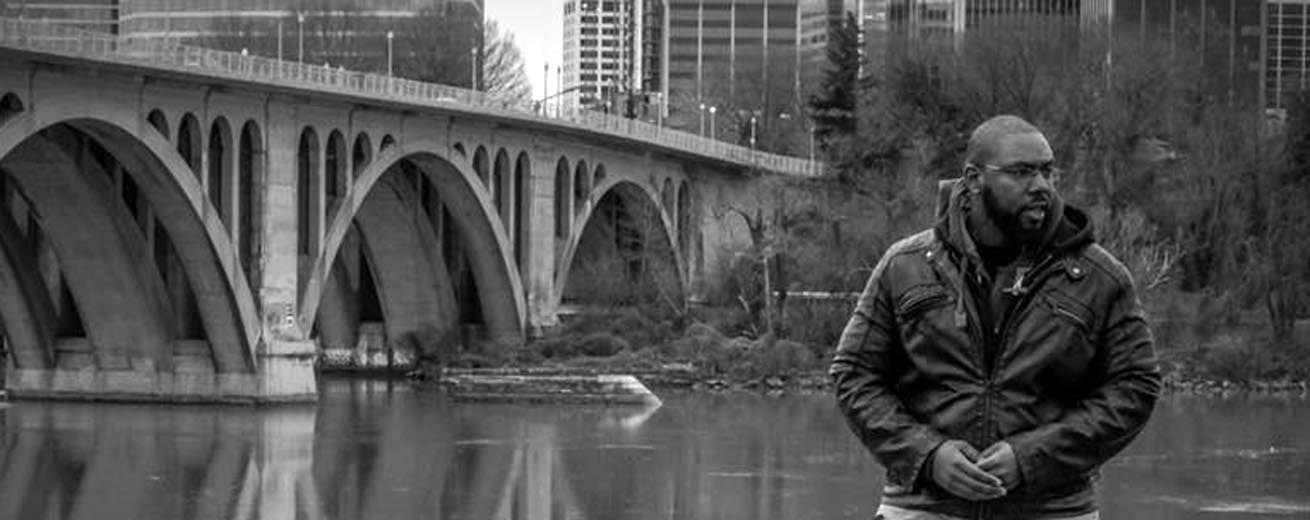 R. Kayeen Thomas' stands on a river bank with a city in the background.