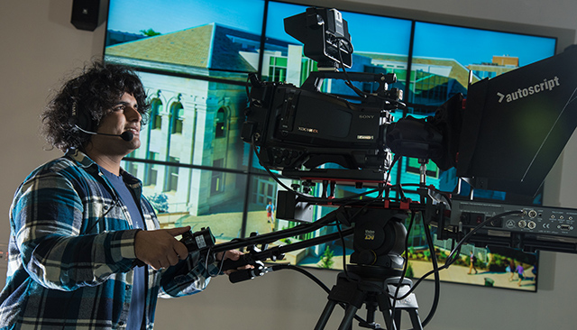 A young man works the studio camera in the School of Communication
