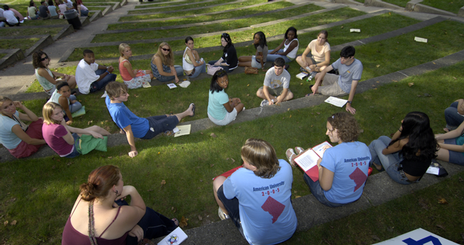 Student sitting on the grass reading and engaging one another
